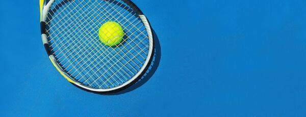 Tennisschläger und Ball auf Hartplatz